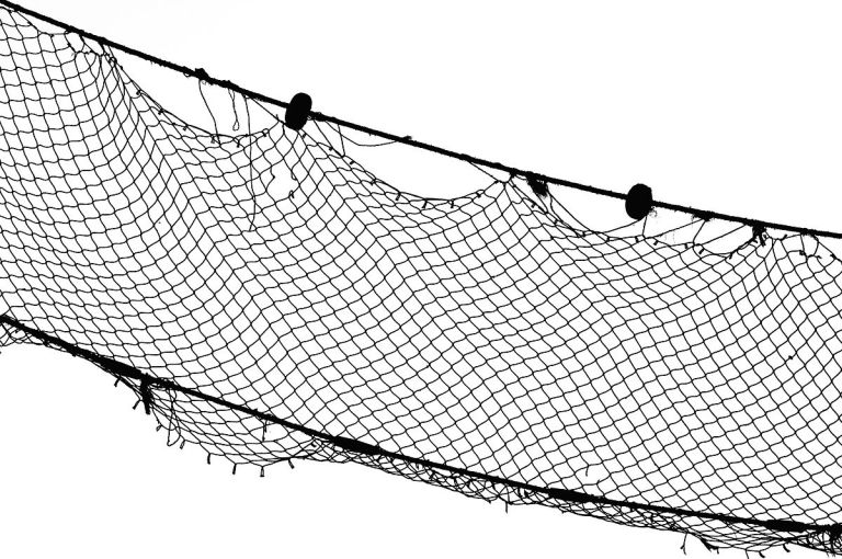 a lage black fishing net on a white background, it is worn in some placed.