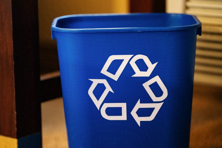 A bright blue plastic recycling bin.