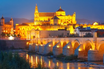 Illuminated Great Mosque Mezquita - Catedral de Cordoba with mirror reflection and Roman bridge across Guadalquivir river during evening blue hour, Cordoba, Andalusia, Spain