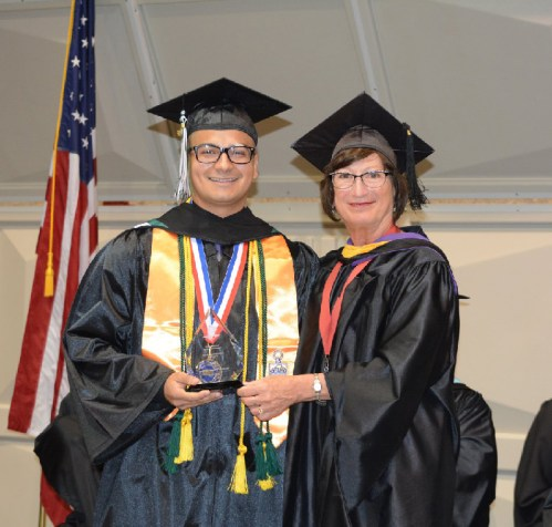 2018 Outstanding Student of the Year Emanuel Serrano accepts his award from VP of Student Services Celeste Donovan.