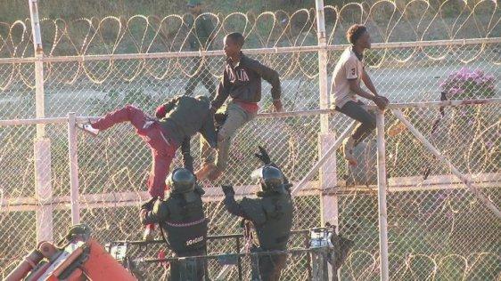 Des migrants traversent la barrière grillagée entre le Maroc et l'enclave espagnole de Ceuta, le 26 juillet 2018. Crédit : Reuters