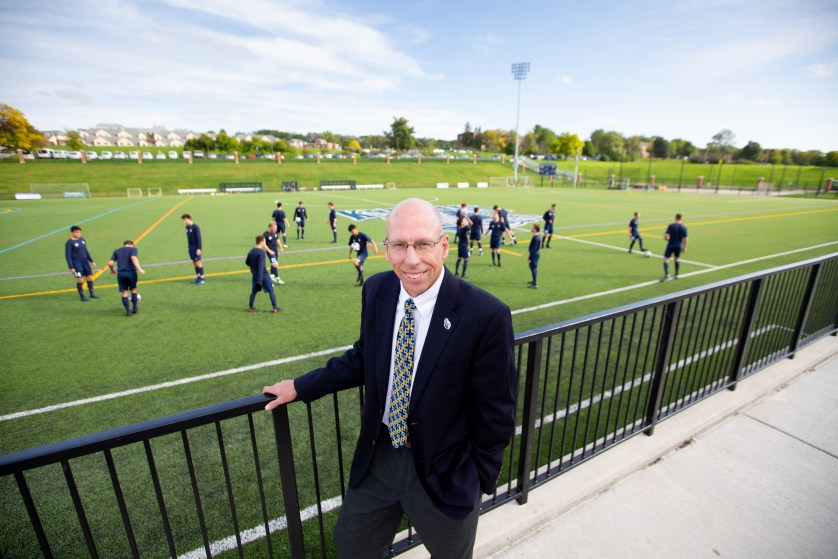Mike Mooney stands in front of the soccer team that is practicing, at the stadium.