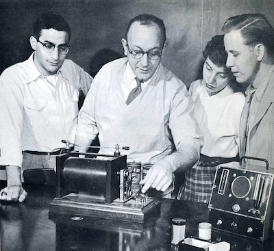 A black and image photo of a professor in 1954 demonstrating a seismograph to students.