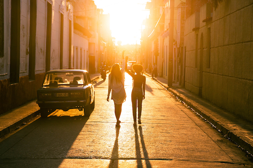 Two students walk down a road in Cuba at sunset