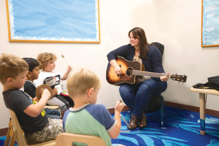 Jamie Sacca Dostal '08 plays guitar for her students.