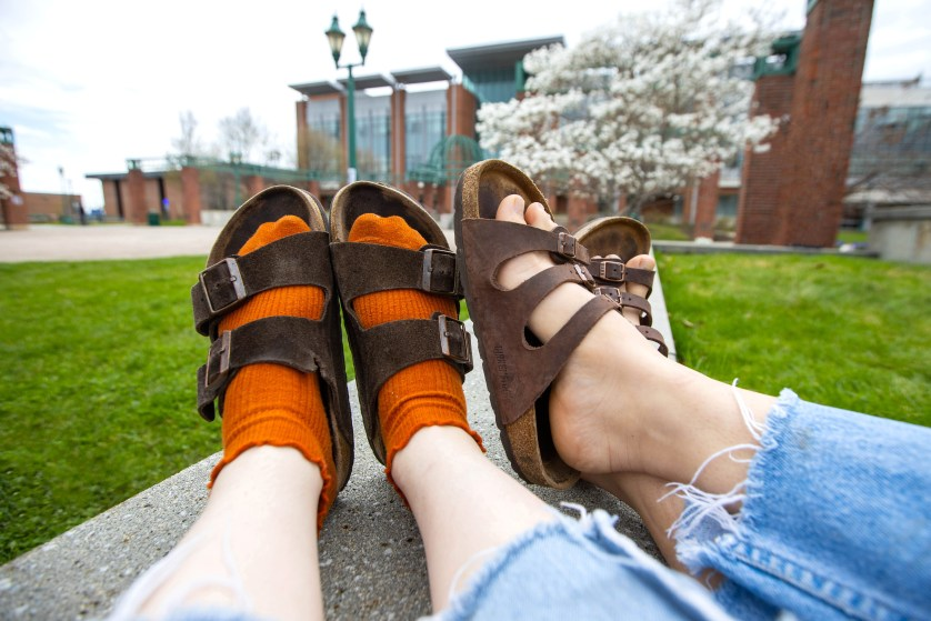 Two students show off their feet in Birkenstock sandals.