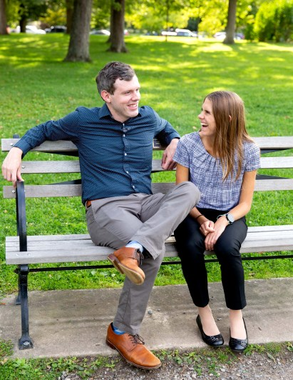 Alex Chichester '14 and Liz Chichester sit on a bench laughing.