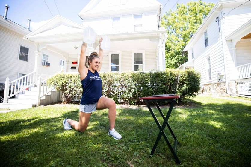 Noelle Staso '21 lifts jugs of water in front of her Geneseo home.