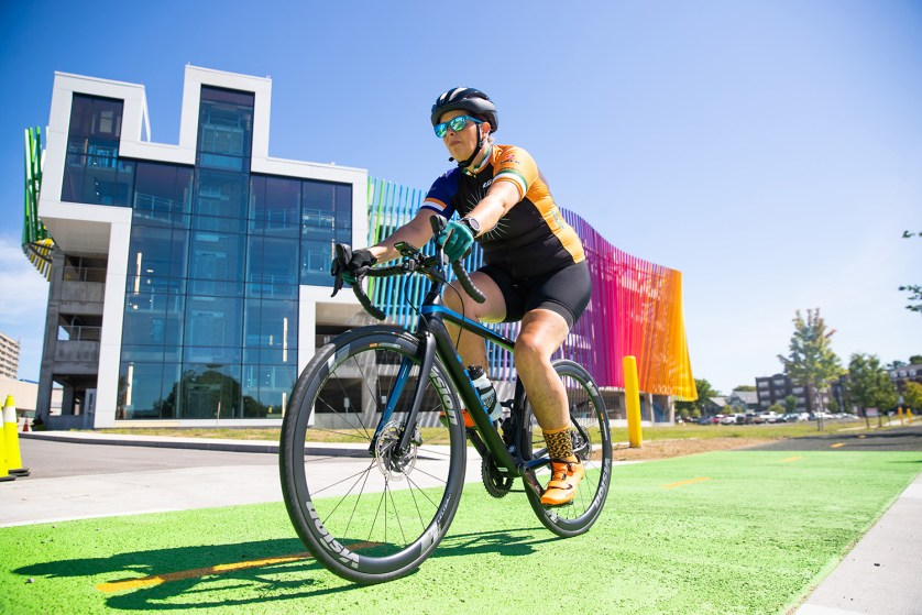 Shana Lydon '98 pedals in front of a colorful building.