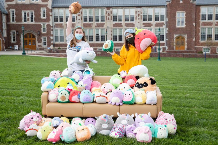 Two students pose with an assortment of Squishmallow toys.