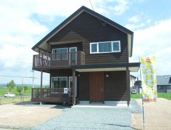 木製サイディング貼りの外装に二階建てのデッキ