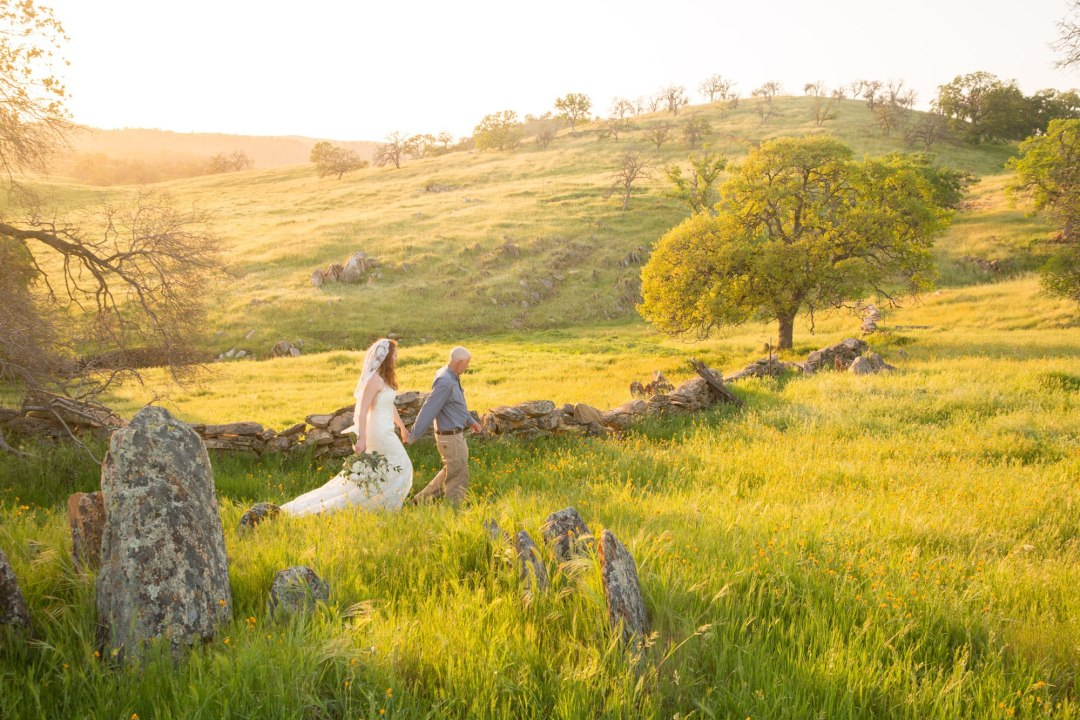Groom leading bride into beautiful rolling hills of green grass and wildflowers - this really reflects how each of our elopement packages can be unique!.