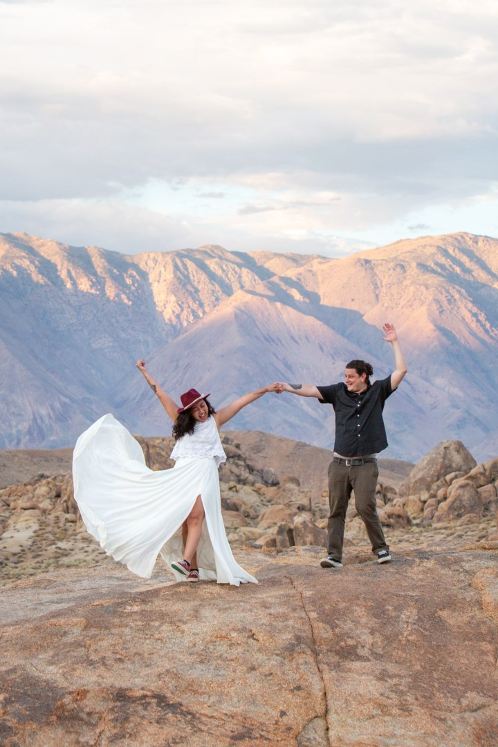 A couple throws their hands in the air to celebrate their Alabama Hills adventure elopement!
