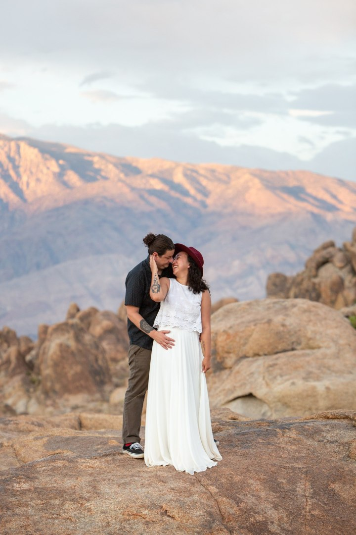 A bride caresses her husbands face as her cuddles her from behind after their adventure elopement in the Alabama Hills.