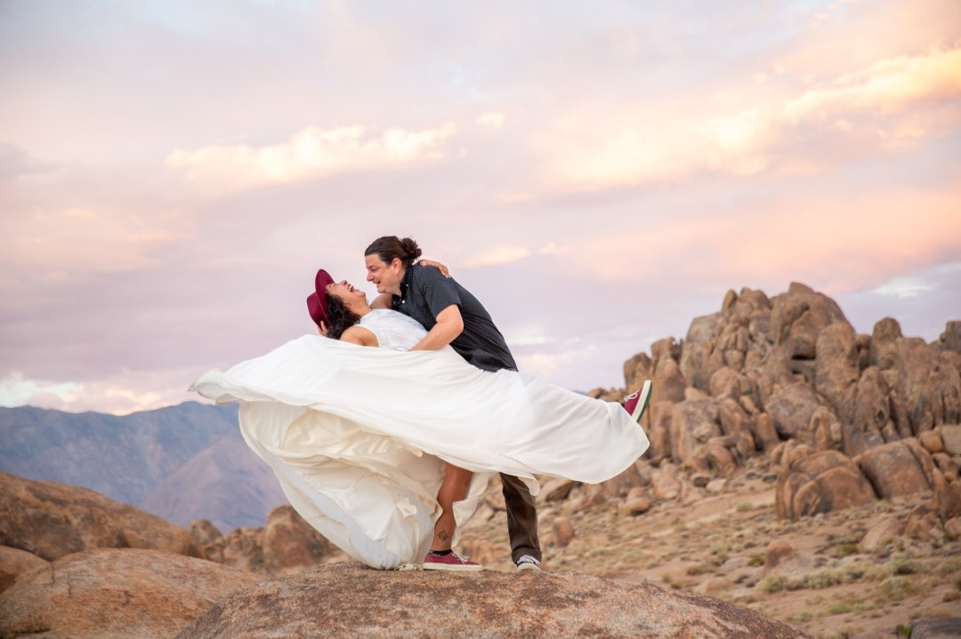 A couple laughs in the Alabama Hills as the man dips the woman back and she swings her white dress around.