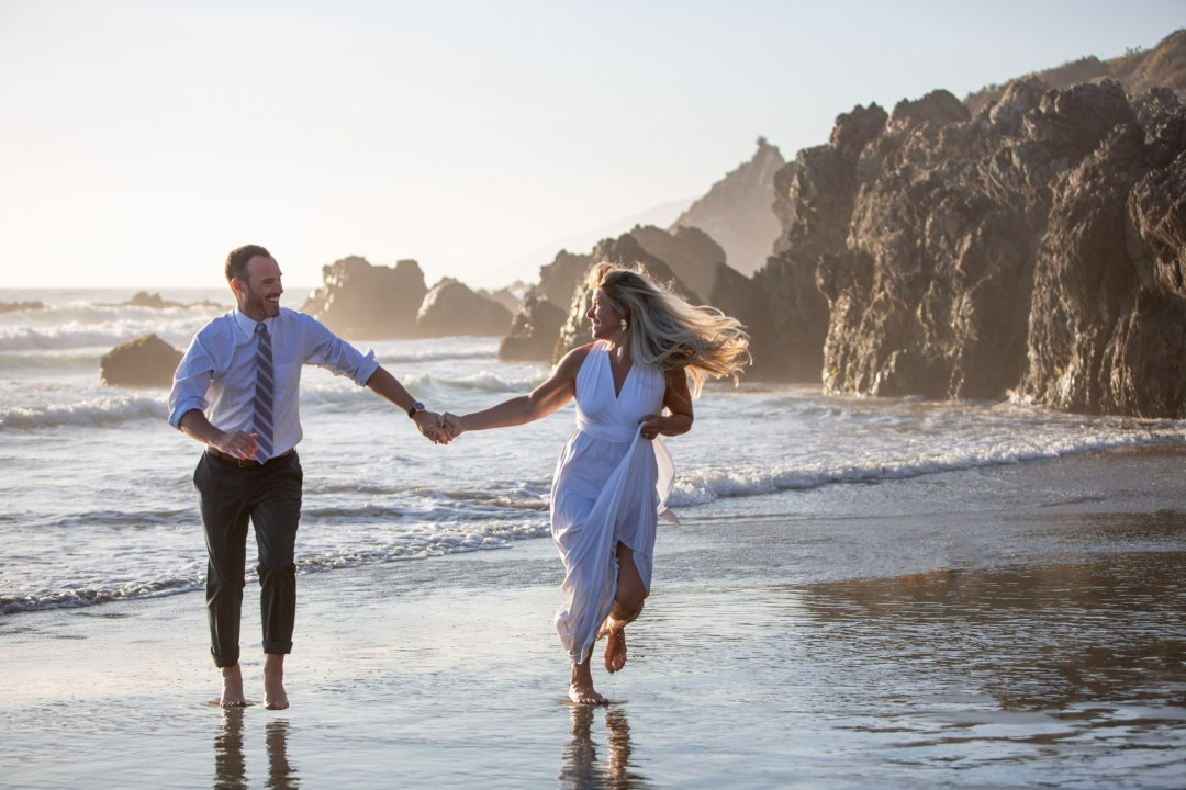 Running on the beach, bride and groom celebrate after a Big Sur Elopement