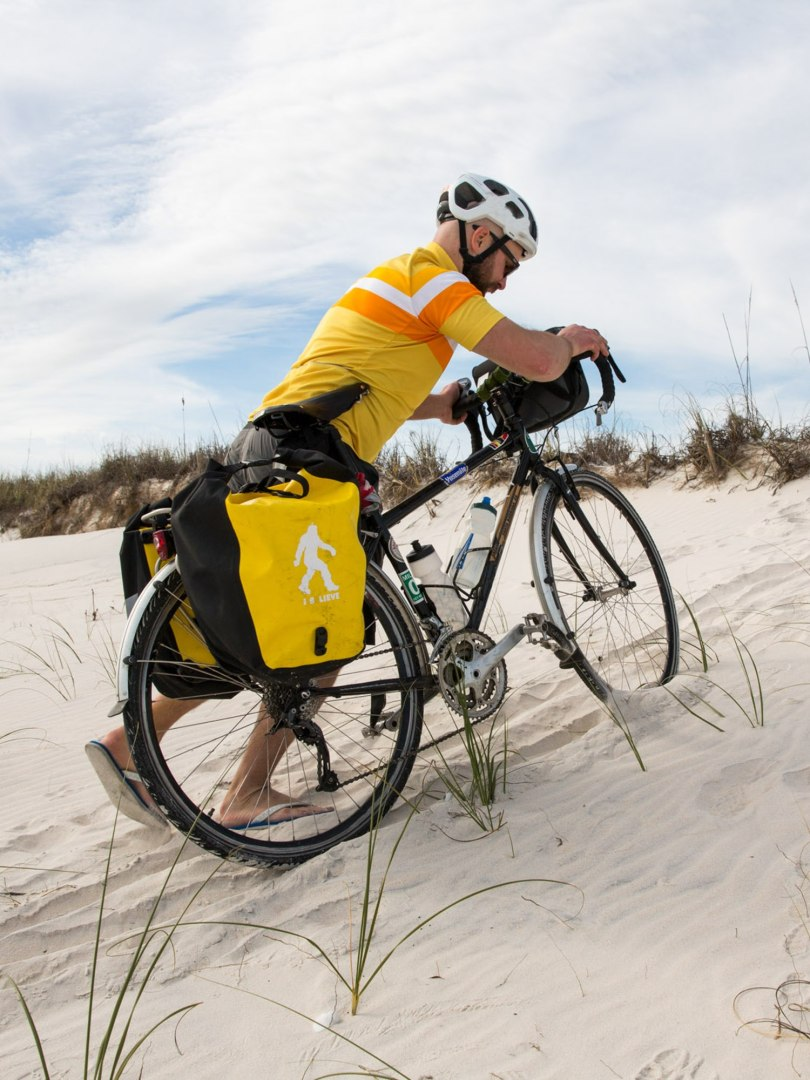 Brian pushes his bike up a sand dune while bike touring the Florida coast.