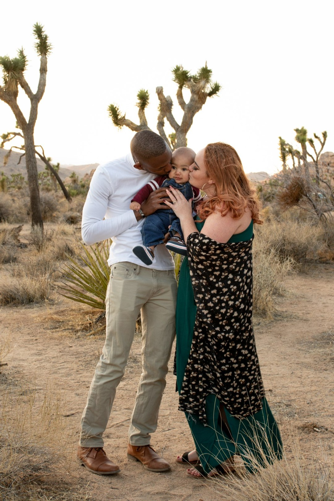 Mom and Dad kissing baby on the opposite cheeks during a Joshua Tree engagement photo session.