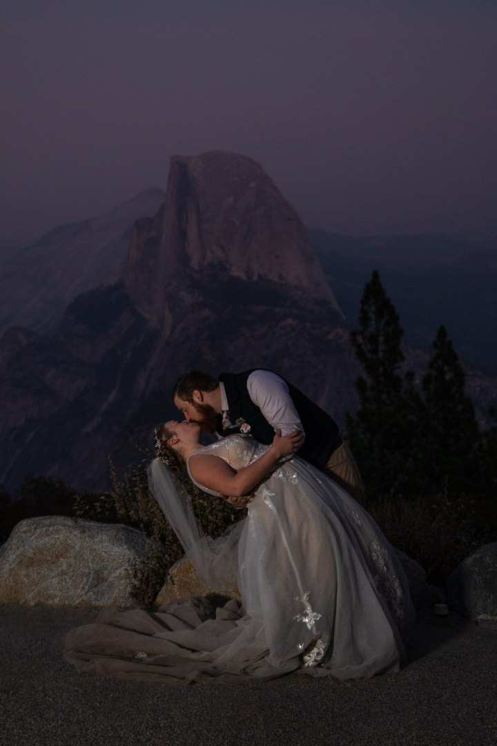 A big dip for a sunset kiss in front of a smoky sunset and Half Dome.