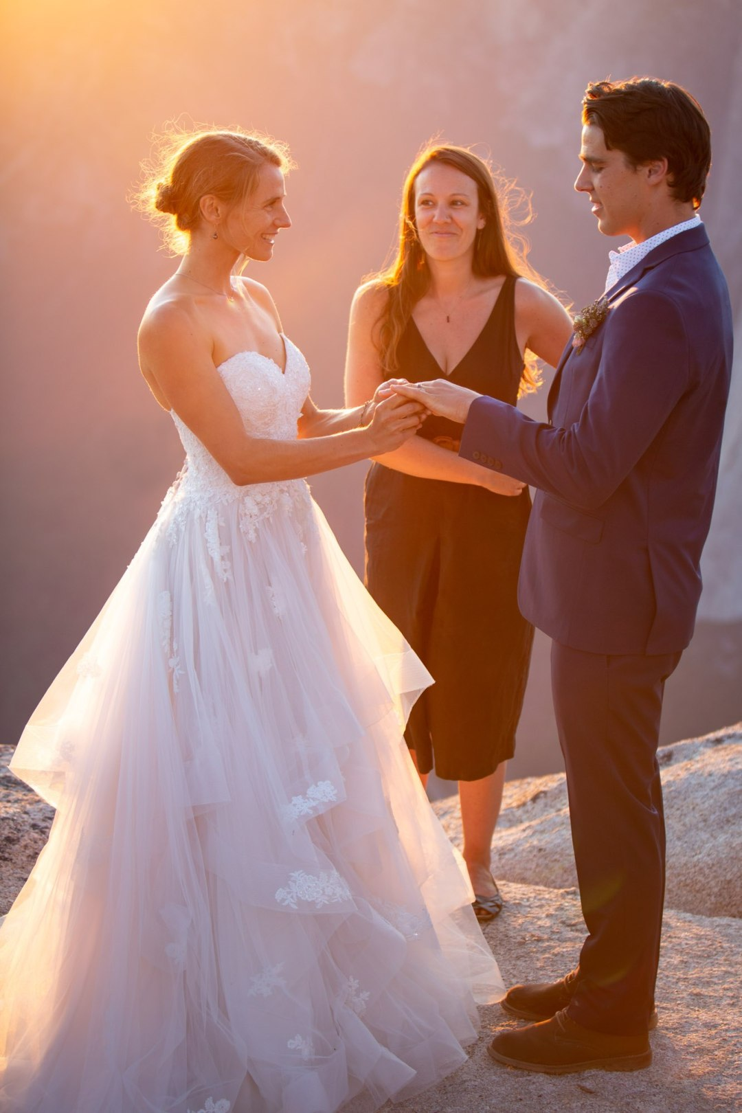 Groom puts ring on bride while officiant smiles