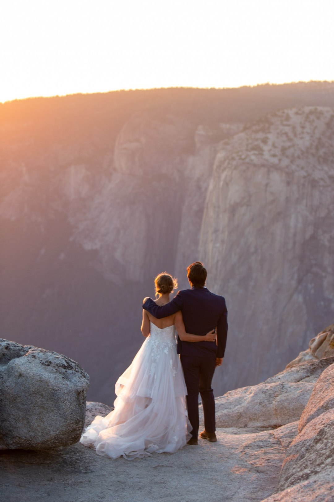 Groom has his arm around bride's shoulder while they stare out over Yosemite Valley