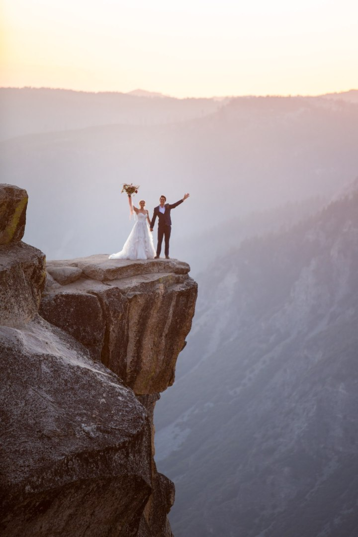 Couple standing on Taft Point with hands in the air. Bride is holding bouquet