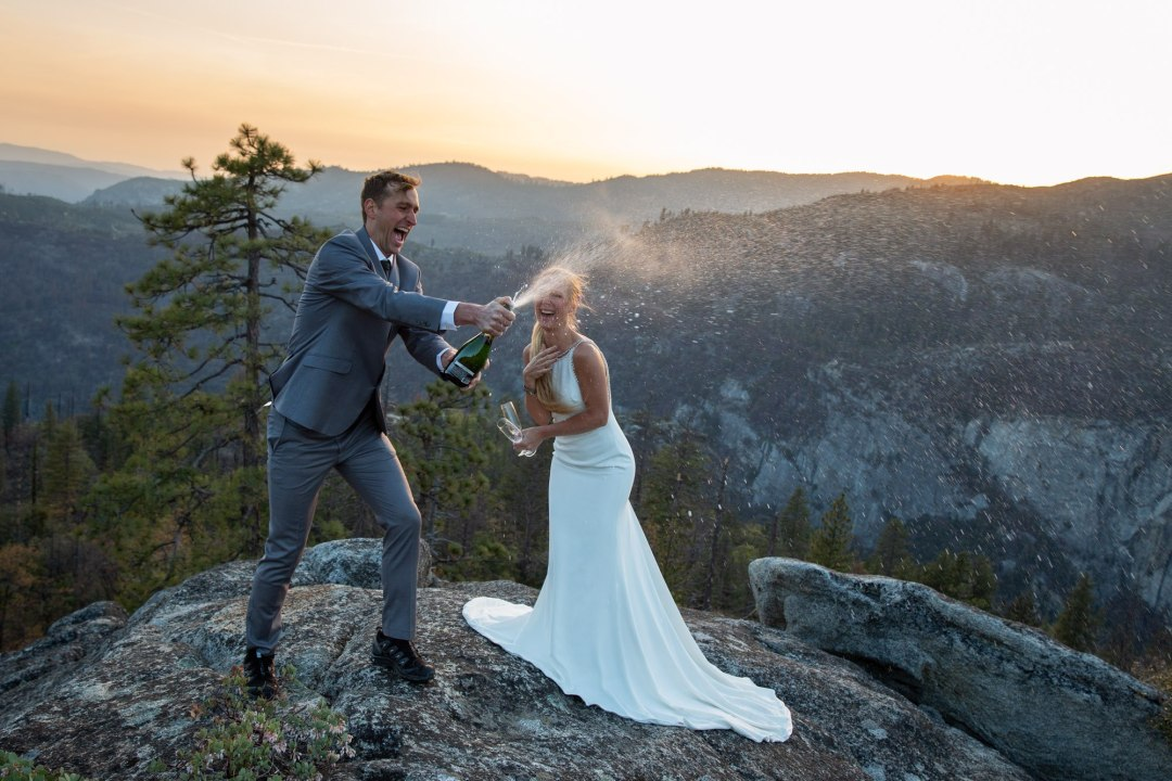 A couple stand on top of a rock, spraying champagne to celebrate saying their wedding vows in Yosemite.