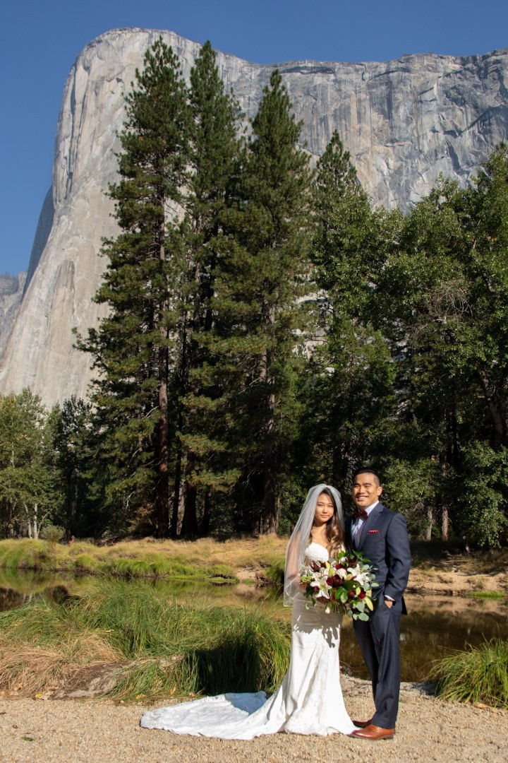 A couple standing on Cathedral Beach with El Capitan in the background
