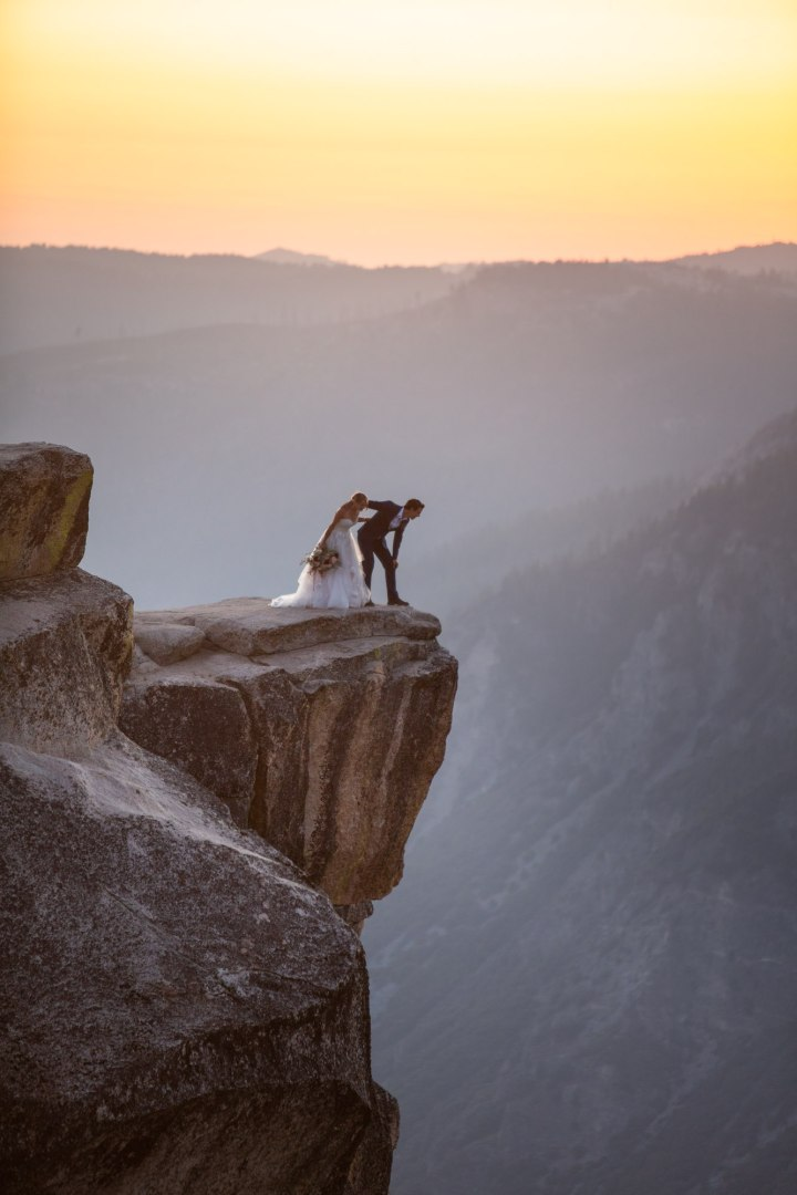 Couple leaning over looking over the edge of Taft Point