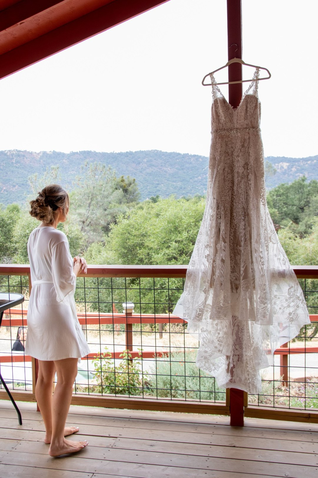 Bride admiring her wedding dress on the deck of her Yosemite airbnb.