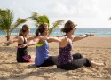 Photo of women doing yoga on the scenic beach