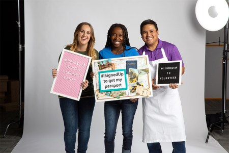 Photo of diverse consultants proudly holding signs showcasing what they have signed up