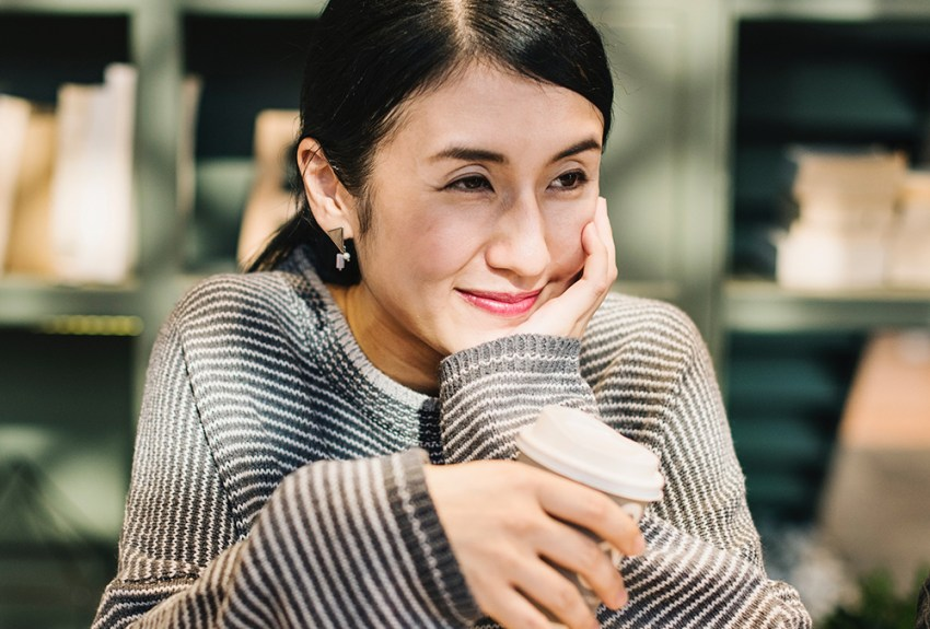 photo of woman reminiscing with cup of coffee