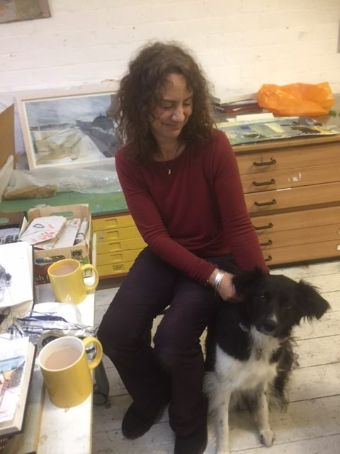 Jane patting her dog Poppy surrounded by artist materials in the studio