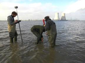 Het plaatsen van een sedimentatiemeter in de weerbarstige turfbodem stelt zijn problemen. Intussen meet Thomas de coordinaten van de toekomstige meetplek op raai twee.