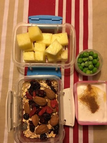 Annanas i tern, skyr med kanel og agavesirup, müsli med mandler, gojibær, tranebær og chiafrø, en lille bøtte med ærter
