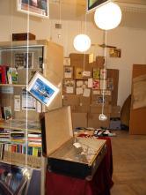 """Der Ausstellungsraum. Links der Bücherschrank: """"Gegen die Regalhaltung""""."""