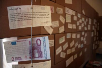 """Auf den Rückseiten der 0€-Scheine stehen Definitionen vom Schenken von den interviewten Personen. Im Hintergrund auf Karton wird die Sammlung der """"Schenken ist...""""-Sätze durch die Besucher_innen fortgeführt."""
