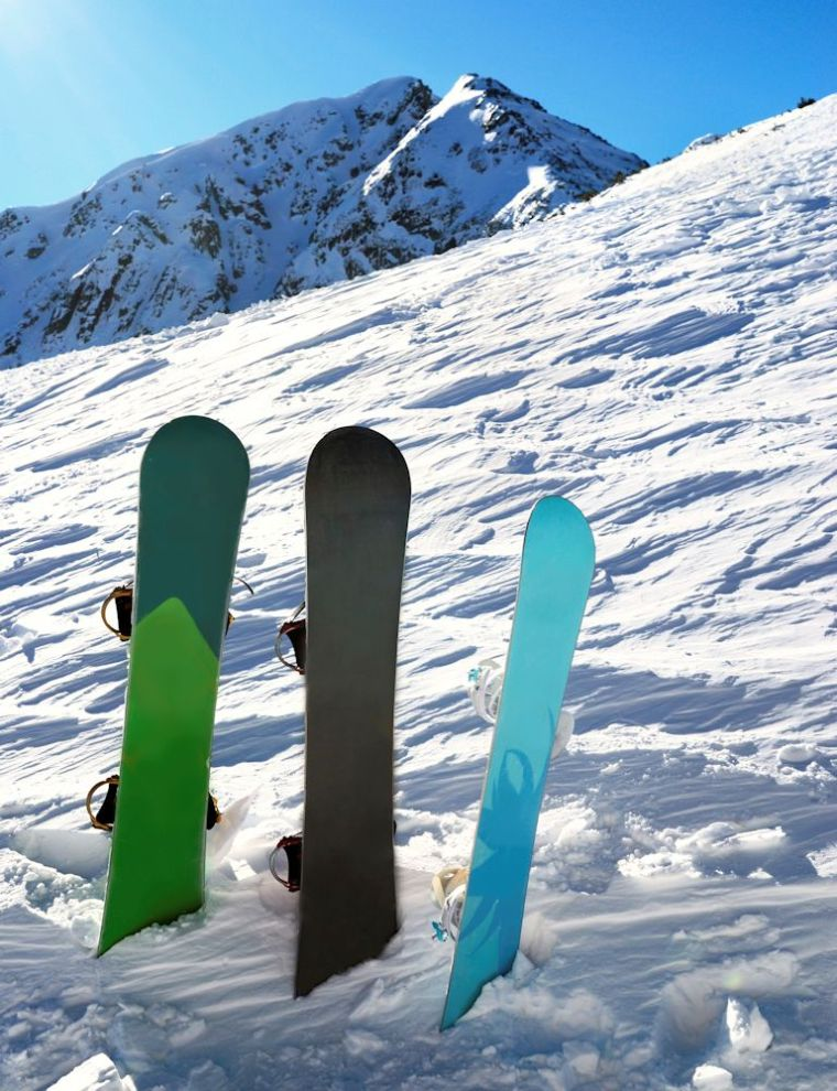 Three snowboards under sun with mountains behind