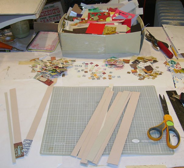 Strips of scrap cardstock and paper scraps ready for gluing