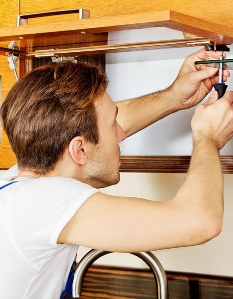 Schober Repair Services | Handyman Services Done Right - Handyman at work repairing cabinets.