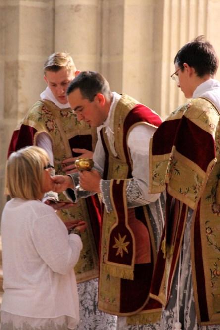 Distribution de la communion par le célébrant.