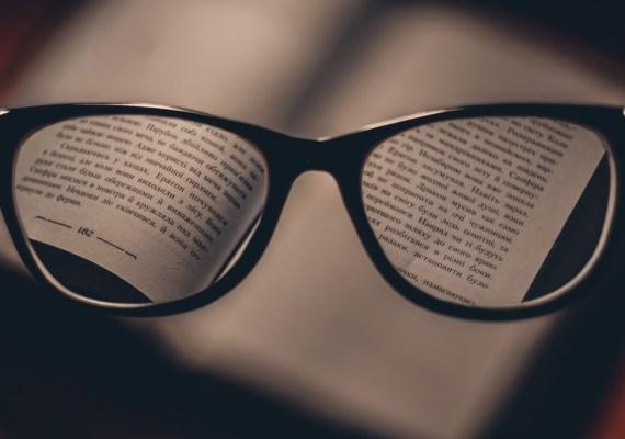 Open book focused through reading glasses