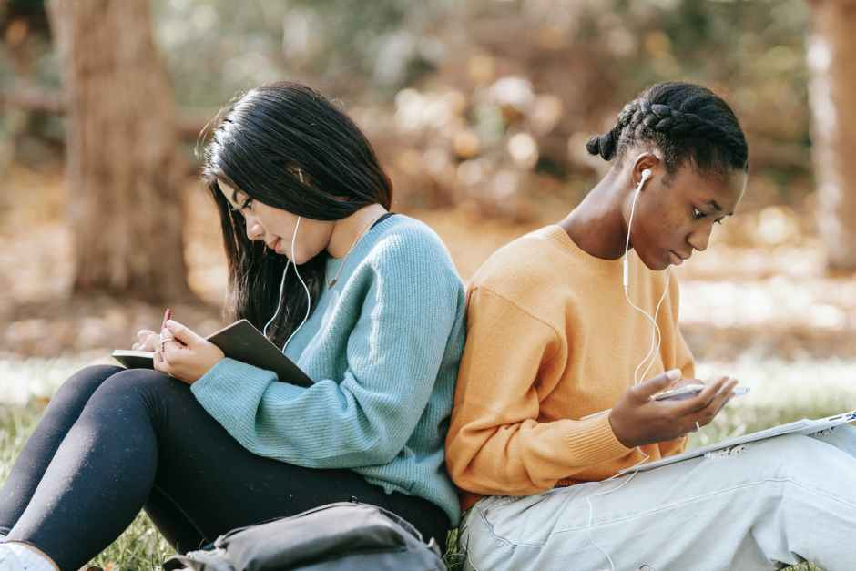 diverse young women studying with smartphone and notebooks
