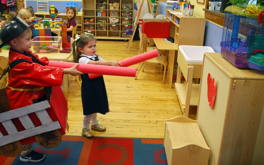 PreK students putting out a pretend fire during class.