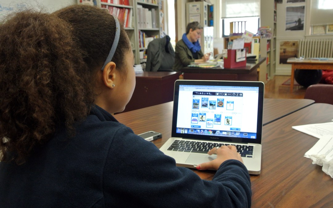 Middle school student researches the olympics on a laptop during project week.