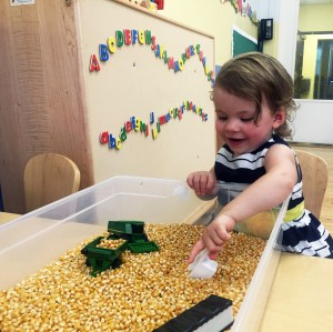 A child playing in a sensory table in learning lab.