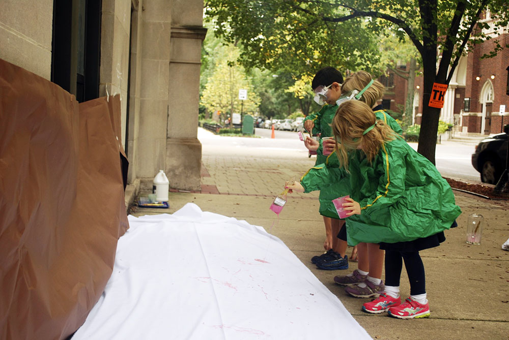 Kindergarten students painting outside.