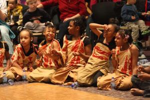 Dressed in authetic clothing, young community members giggle and listen while sharing stories and anxiously awaiting their performance at a previous Multicultural Fair in the Diponio Room.