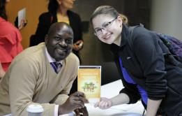 """PHOTO BY NATHAN GARTNER PHOTO EDITOR Kaguri, left, poses with Raya Lasiewski, holding a copy of his book """"The Price of Stones: A School for My Village."""""""